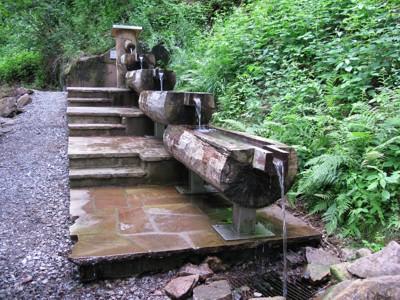 Nachdem das Wasser aus dem Quellstamm austriet, läuft es über vier Becken abwärts