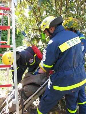 Ein Verletztendarsteller wird mittels Bergewanne und Rollgliss aus dem Regenwasserrückhaltebecken gerettet