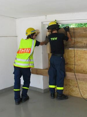 Zwei Helfer verschließen ein beschädigtes Schaufenster provisorisch
