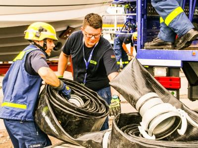 Björn Fellhauer (rechts) und ein weiterer Helfer verladen Druckschläuche