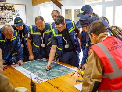 Björn Fellhauer und weitere Führungskräfte besprechen die aktuelle Lage mit einer Landkarte