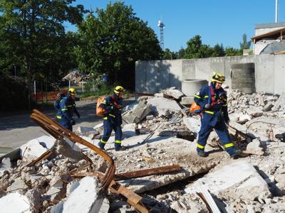 Drei Helfer betreten das Trümmerfeld, um nach vermissten Personen zu suchen.