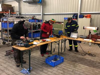 Drei ehrenamtliche Helfer prüfen die Sicherheit elektrischer Geräte