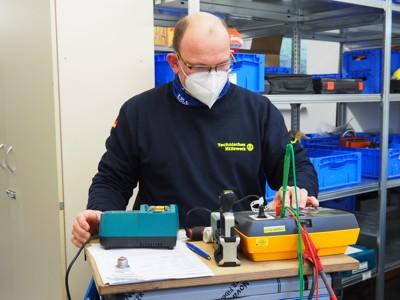 Ein hauptamtlicher Mitarbeiter der Regionalstelle Mannheim prüft ein Elektrogerät